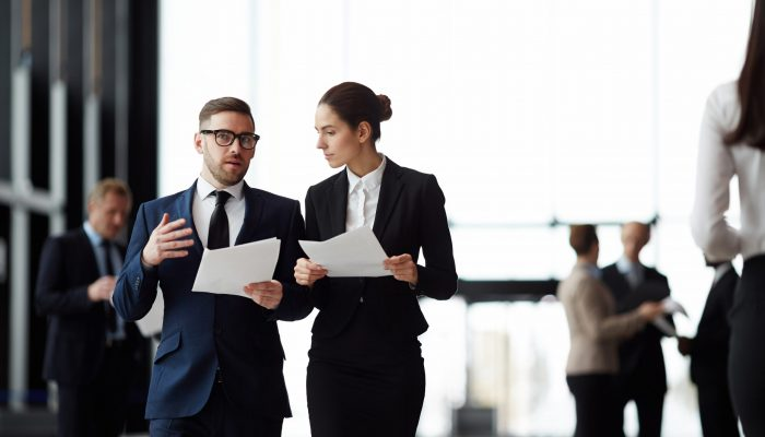 Businessman with papers consulting with young female colleague while walking to conference